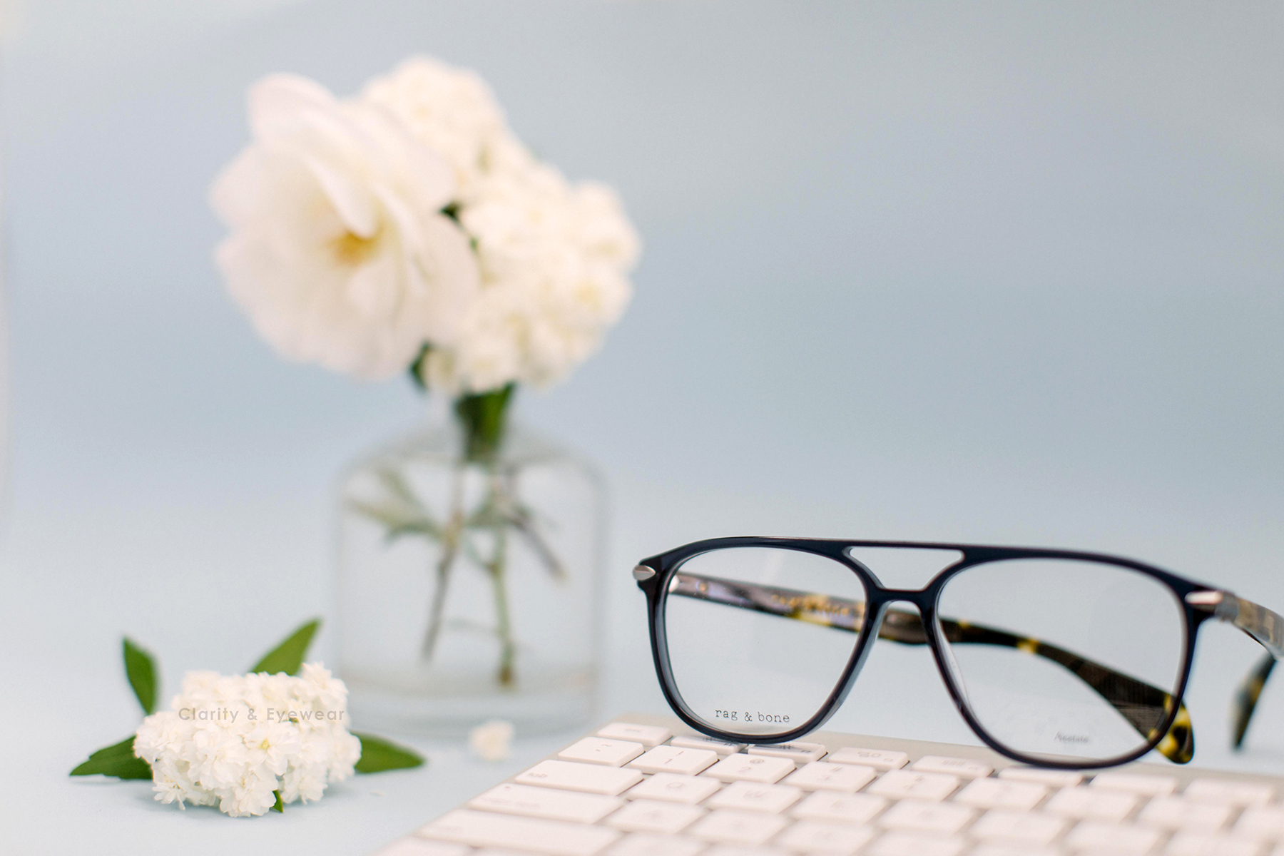 Black optical glasses sitting on top of white keyboards with a vase of white flowers next to it