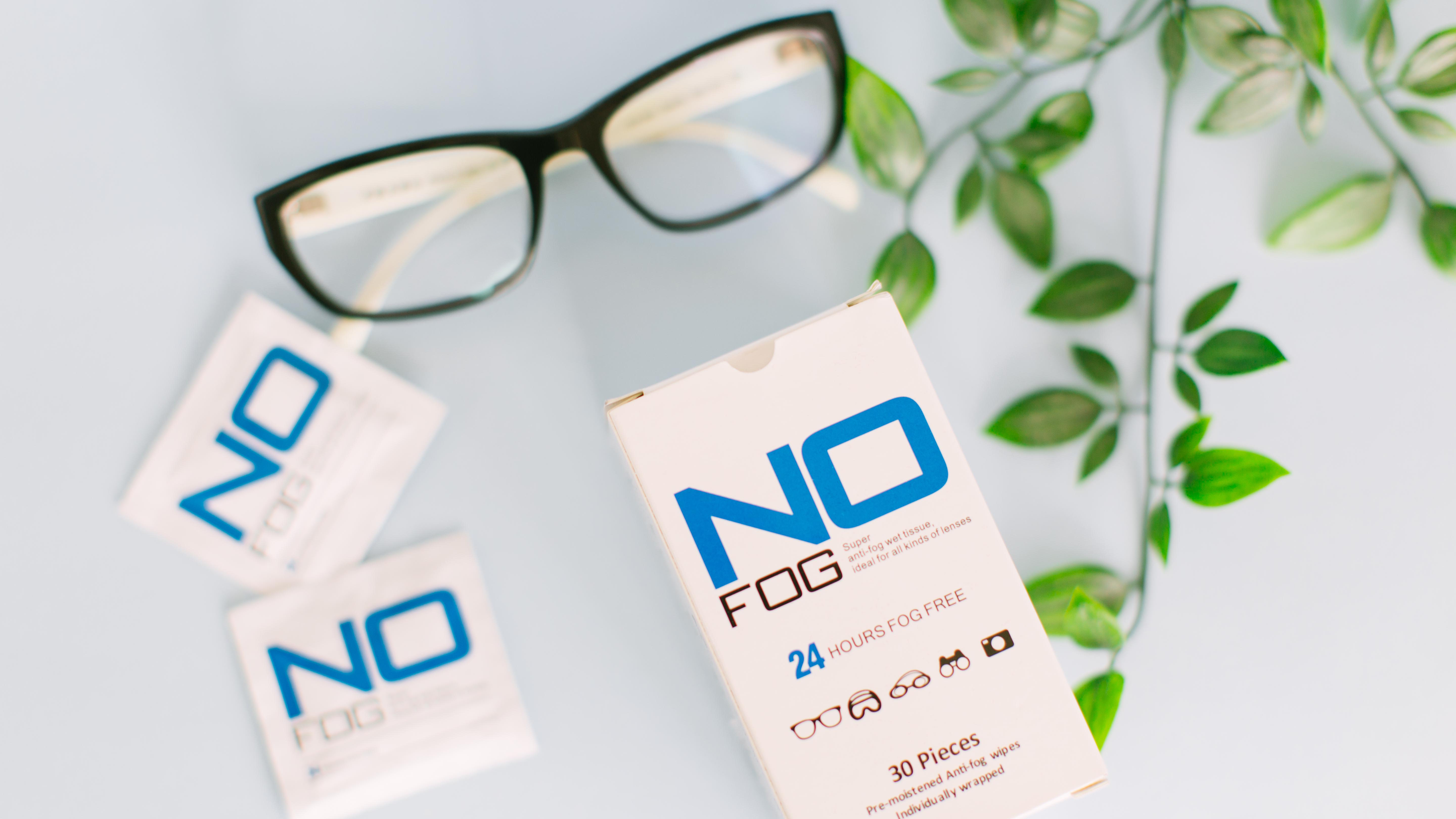A box of anti-fog wet tissue with some anti-fog sachets  & a pair of black optical glasses